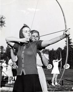 The coach helps a girl on the archery team with her aim, 1942.