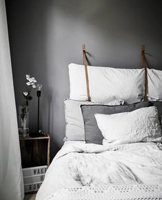 I really like the contrasting grey wall with the clean White bed spread. Balances out the room and creates just enough contrast.