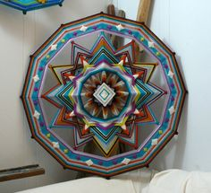 24 inch, 12 sided Ojos de Dios by Jay Mohler with wool yarns and metallic highlights