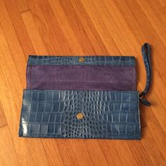 Blue leather Saks clutch Beautiful clutch used only a few times!  Measures 14 inches across and 6 inches tall. Magnetic closure on top center inside. 3 pockets inside, one zippered and two open. Zippered closure with great handle. Beautiful! Saks fifth avenue Bags Clutches & Wristlets
