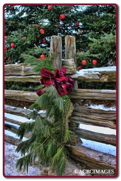 evergreen swags decorating the fence along the lane that leads to your barn wedding venue