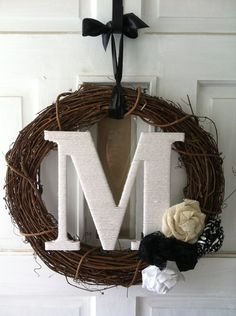 Custom Monogram Wreath. $35.00, via Etsy - but spray paint a regular wreath white and wrap the letter in twine?  And add...a snowflake?  Hmm... Or get one of these brown wreaths, do the letter in red yarn after painting it, and then add snowflakes rather than the roses?