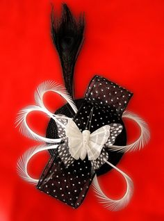 Tocado con base negra, pluma pavo real negra, plumas biots blancas, cinta negra con topitos y mariposa blanca.