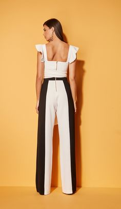 Calça pantalona confeccionada em crepe com detalhe preto na lateral. Seu fechamento é em zíper na parte traseira.   Composição: 100% poliéster.