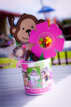 Baby formula cans covered in a custom label that I created, filled with monkey pops and candy flowers.