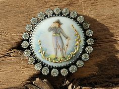 18th century hand painted ceramic button, featuring a gentleman dressed in tail coat and tricorn hat, holding a monocle to his eye, with gold painted swirled decoration around the base. Surrounded by 23 paste stones. Raised DEPOSE registration mark on the reverse.