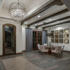 Entering the home, you'll find this beautiful dining area nestled in the corner. Gray hardwood flooring and wood beams add rusticity to the transitional design. A herringbone pattern inlaid in the hardwood floor is a lovely statement at the front door.