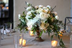 Low posy centrepiece in small urn surrounded by varied heights of  mercury glass votives.