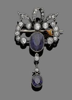 A sapphire and diamond brooch, circa 1900 The openwork brooch, millegrain-set with old brilliant, rose and single-cut diamonds, centrally set with a cushion-shaped sapphire, suspending a similarly-shaped sapphire, mounted in silver and gold
