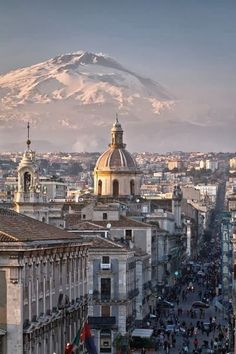 Catania, Sicily. and Mt. Etna volcano covered by snow in the background.