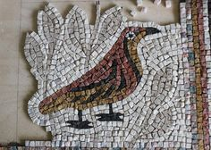 Riven bird - a direct method mosaic of a brid with a leaf background done using the riven (cut) side of the stone exposed. www.helenmilesmosaics.org