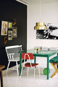 Gold light, black wall, and green table, red chair, white vintage bench