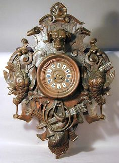 a handcarved wood wall clock decorated with wild birds and a dog head, ca. 1900.
