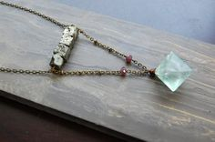 Diamond cut fluorite crystal hangs low from a line of 4 square shaped pyrite crystals. Made with antique bronze chain measuring 28 long.  >Fluorite is
