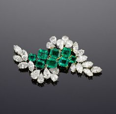 A diamond and emerald brooch, by Chaumet, circa 1960  Of abstract cluster formation, centrally set with two graduating rows of step-cut emeralds, each side highlighted with randomly set pear and marquise-cut diamonds, diamonds approximately 8.25 carats total, signed Chaumet, length 5.5cm.