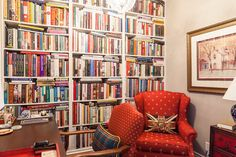 "The front foyer and home library. ""My tiny library is my favourite part of the space. I am an avid reader and a total bibliophile. I wanted this space to feel warm and enveloping (just like a good book) and I think that the use of the colour red really helps achieve this."""