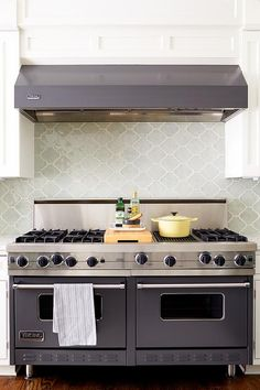 Fabulous kitchen features a gray Viking hood which stands over a gray glass arabesque tile backsplash stands and a gray Viking dual range.
