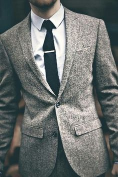 A speckled grey suit with a tie clip on a black tie.