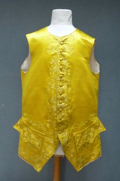 Waistcoat, China for the Western export market, 1760s. Bright yellow satin, embroidered in twisted silks with peonies and fruits in a leaf meander, continuing to the skirts,  satin stitches but with some Peking Knots, the buttons embroidered with strands of silk, embroidered buttonholes, the pointed shaped pockets with central peony flanked by seed heads and other small flowerheads, with similar detail below pockets, linen lining.
