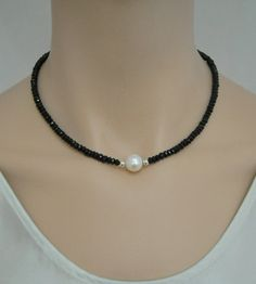 Elegant yet simple, sparkling faceted black spinel necklace with a large, lustrous white freshwater pearl at the center, flanked by sterling silver beads. Pairs well with almost any kind of outfit, from casual clothes through business attire to evening wear. The necklace is 16 inches long (choker length) and features 5 - 5.5mm faceted spinel rondelles, a 10.5mm pearl and a large, sterling silver lobster claw clasp. Every piece purchased from Silver Serenade comes in a lovely silk pouch…