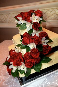 Delicious vanilla cake with buttercream icing decorated in a waterfall of fresh red & white roses for a lovely birthday party.