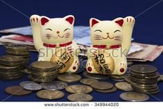 "Two lucky cats (Maneki-Neko) among money. Inscriptions on the tablets ""money luck"" and  ""ten million ryo"" (ryo - old Japanese coin). Background is blue."