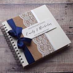 HESSIAN LACE & BOW WEDDING GUEST BOOK Rustic guest book decorated with natural hessian/burlap, pretty ivory lace and a hand-tied satin bow in your colour choice from our colour chart above. Personalised on Ivory card set in the centre upon ivory satin ribbon Hardback ring/wire
