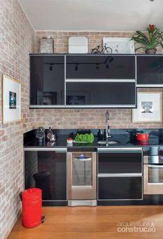Na cozinha, as portas empregam perfil de alumínio e vidro preto (Fernando Sirlei Marcenaria), e a bancada, granito preto absoluto (Irmãos Feital). Projeto Escala Arquitetura e André Passini.