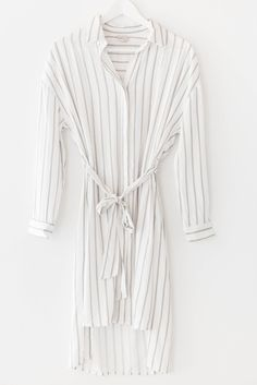 Long sleeve striped dress with a collared neck and button up front. Featuring an a-line silhouette with a self tie waist and side slits. Cool and lightweight cotton material making it perfect for summertime! Available in white/taupe or white/navy.  70% Cotton 30% Linen Imported