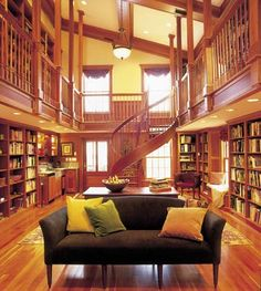"huge two-story home library with wood balconies and spiral staircase. hello, awesomeness...i've been expecting you.... very warm ""Color isn't always about paint, as this Hatfield, Massachusetts, library demonstrates. The warm reddish-orange tones of the cherry bookcases, beams, and flooring envelope the room, making a large space feel cozy and intimate."""