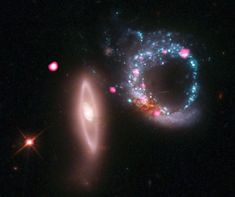 Similarly, the fuchsia blobs on this image are regions of intense X-ray radiation, thought to be black holes that formed when two galaxies (the blue and pink rings) collided.