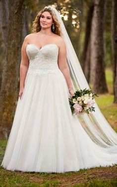 This satin A-line plus size wedding dress by Stella York has a princess cut strapless sweetheart bodice with clear beading on lace that catches the light. The tulle skirt fans full into a sweep train. Choose from a corset closure or a zipper closure under fabric-covered buttons.