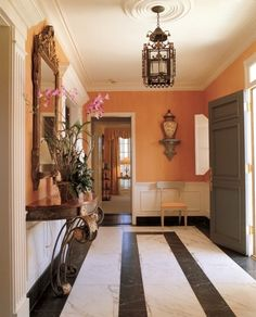 Foyer with salmon walls, black and white floors, antiques - Bunny  Williams