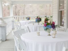 Is there anything more Southern than guest tables on a white wrap around porch? | Photo: Love Behind the Lens Photography