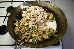 Varm en wokgryde godt op og steg kyllingestrimlerne i olie i ca. 2-3 minutter sammen med finthakket hvidløg og finthakket chili. Krydr med salt og peber. Tag kyllingestrimlerne op af wokken. <BR> <BR