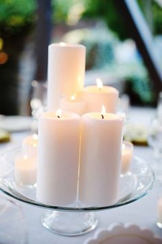 different sized pillar candles on a plate or mirror