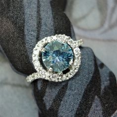 "A Colorado topaz & diamond engagement ring.  Our client proposed with a simple silver ring using the topaz faceted in our studio.  Once she said ""YES"" they designed a sweeping ring bedazzled with diamonds and mill-grain."