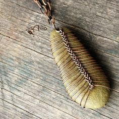 What a wonderful and stunning way to wrap an undrilled or pretty beach stone. I love it, seems a stone feather
