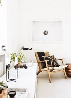 raw wood, patterned pillow and a bright white room - a serene sitting area.