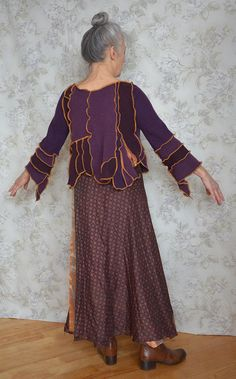 **This little mauve jacket has a lot of details made with yellow seams. Its made from merino and lambswool. Also there are two little surprise pieces from sari fabric with little mirrors. The sleeves are shorter on the front side and pointy at the back. *Bust: 36 (92cm) *Sleeve (front