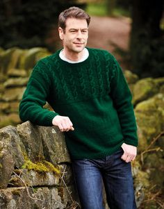 Shown in a rich green, this drop-shoulder sweater was designed for the Hayfield Bonus Aran brochure by Sirdar. Now in acrylic, the newest yarn addition to the Hayfield family creates a gansey feel with the cabled chest pattern. Halloween Men, Sock Shop, Cross Stitch Supplies, Dress Gloves, Sweater Knitting Patterns, Yarn Brands, Men's Wardrobe, Jumpers For Women, Cable Knit Sweaters