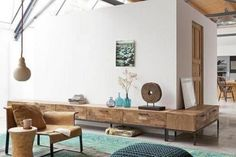 Rustic mix of wood grains, geometric rectangular low sideboards with simple, metal legs; Love the circular art piece next to the blue glass bottles.