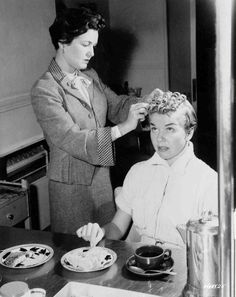 Medium BTS shot of Doris Day as Ruth Etting eating while woman does her hair.