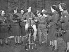 """UNITED KINGDOM - OCTOBER 30, 1940: Women drivers of the American Ambulance-ONE HOLDING A BLACK CAT, Great Britain organization in London enjoying the demonstration given by one of their comrades, Mrs Winifred Denny, of an electric cycle machine which the girls have just acquired. The apparatus, which behaves very much like a """"Bucking Broncho""""., will now play its part in keeping the girls fit.' (Photo by Planet News Archive/SSPL/Getty Images)"""