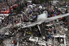 Las fuerzas de seguridad y los equipos de rescate examinan los restos de un avión de transporte C-130 Hércules militares indonesios después de que se estrelló en una zona residencial en la ciudad del norte de Sumatra de Medan, Indonesia. 30 de junio de 2015. Al menos 30 personas murieron cuando el avión se estrelló en una zona residencial. Roni Bintang—Reuters