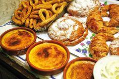 Crema catalana, receita popular de creme frio catalão com um revestimento de caramelo crocante. Ao fundo churros e ensaimadas.  Na cozinha catalã, a crema catalana (creme catalão) ou crema cremada (creme flambado), é um prato semelhante ao crème brûlée.  É tradicionalmente servido no dia de São José (março 19), embora hoje em dia ele é consumido em todas as épocas do ano.  O creme é aromatizado com limão ou raspas de laranja e canela. O açúcar na crema catalana é tradicionalmente…