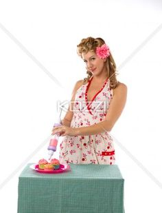 portrait of a young woman decorating cupcakes. - Portrait of a young woman decorating cupcakes against white background, Model: Carrie Galbraith