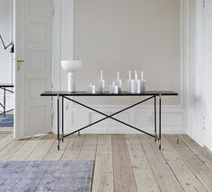 The slim, sleek console table is a modern take on a tile top table, with four pieces of marble mounted end-to-end in a long and slender metal frame.