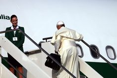 Off to Brazil: Pope Francis carries his own bag onto the plane.