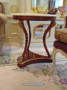 Lot 981 - Empire style mahogany and parcel gilt marble top occasional table on a tri-form base 600mm x 840mm